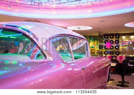 Bar decorated by old pink car and phonograph record.