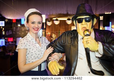 Beautiful young woman in retro dress with waxwork singer in black suit