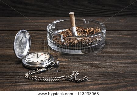 Vintage pocket watch and crumpled cigarette in glass ashtray on the old wooden table