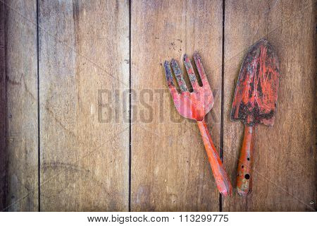 Small Gardening Shovel And Fork On Wooden Grunge  Background