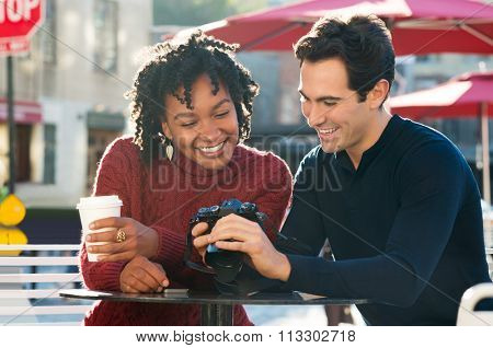 Happy young tourist couple looking at pictures in their camera in a cafe. Smiling couple looking at their photos on the screen of camera in the cafe outdoor. Multi ethnic couple sitting at cafeteria.