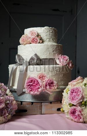 Wedding Cake With Flowers And Wood Pallet