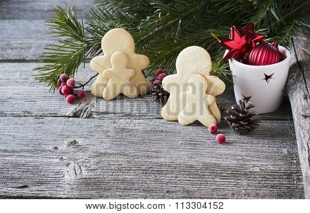 Homemade gingerbread men on a simple wooden background with fir branches