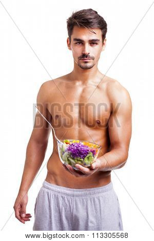 Portrait of a fit man holding a bowl of fresh salad on white background