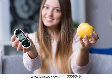 Holding Glucometer And Apple