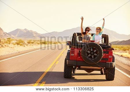 Friends On Road Trip Driving In Convertible Car