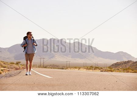 Man On Vacation Hitchhiking Along Country Road