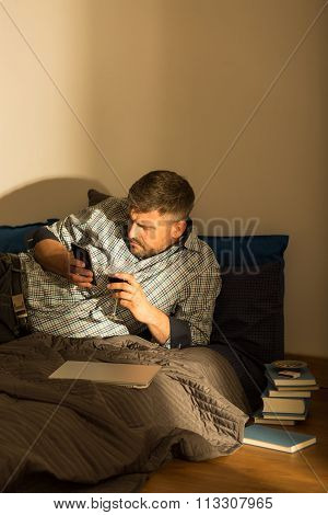 Man Texting On Bed
