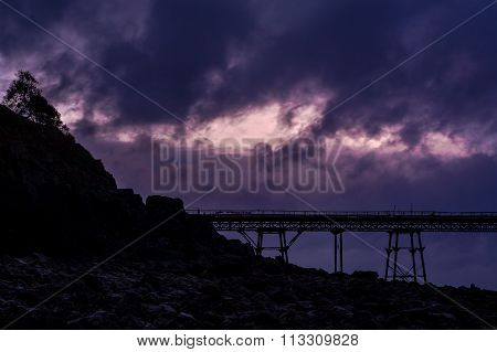 Silhouette of Birnbeck Pier, in front of an angry sky, at Weston-super-Mare
