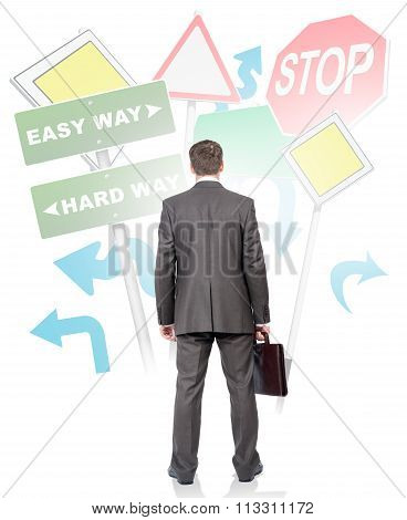 Businessman standing in front of road signs