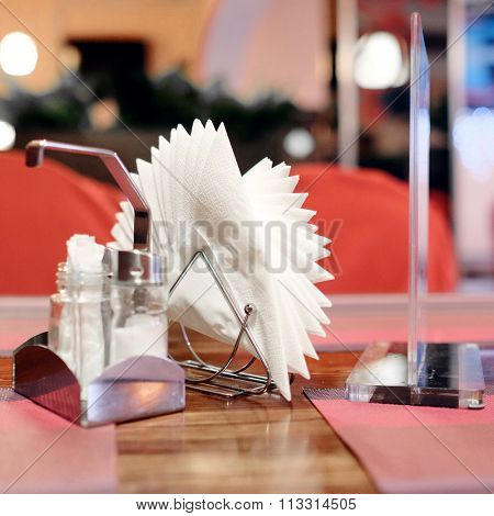 On an empty table in the restaurant napkins, salt shaker and pepper