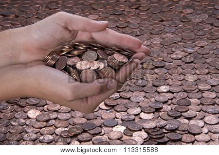 hands holding pennies over background of pennies