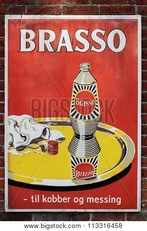Old style tin advertising board for Brasso metal polish on a wall