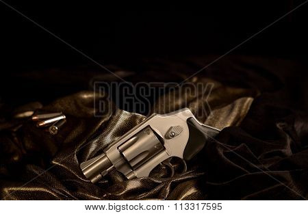 Revolver With Bullets On Satin