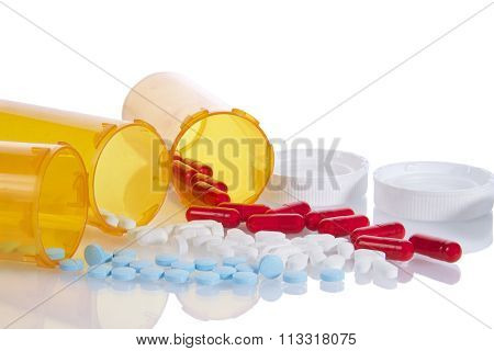 Three Prescription bottles spilling medication pills onto a reflective surface