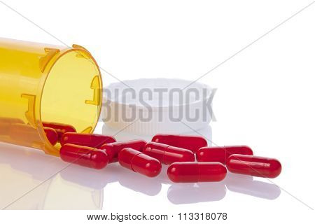 medication bottle on side with pills spilling out onto a reflective surface.