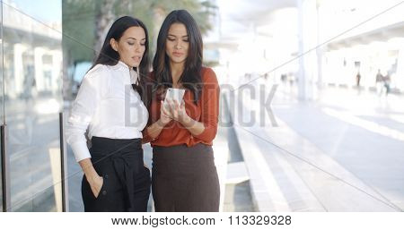 Two businesswomen checking a text message on a mobile phone as they stand alongside a store window in a high key urban esplanade