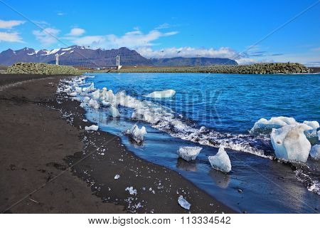 Ocean surf on the beach with black sand. Ice floes in the sun shine
