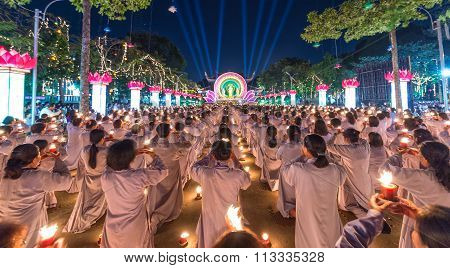 Buddhists offer candle in the night to Buddha Amitabha