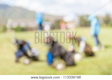 Blurred Photo Of Golf Bags Over The Green Field Background, In Golf Tournament.
