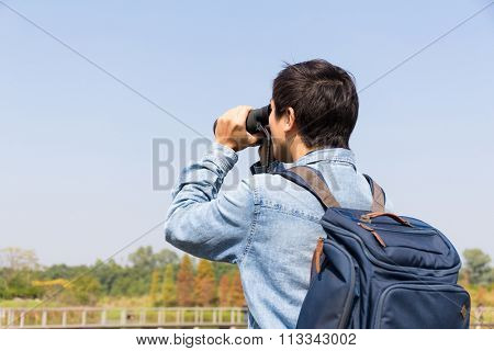 The back view of the Man looking though binocular