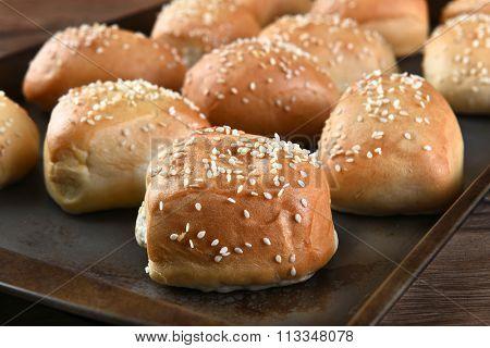 Closeup of fresh baked sesame seed dinner rolls on a metal baking sheet.