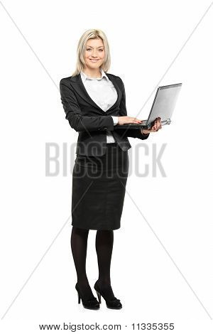 Full Length Portrait Of A Beautiful Businesswoman Working On A Laptop