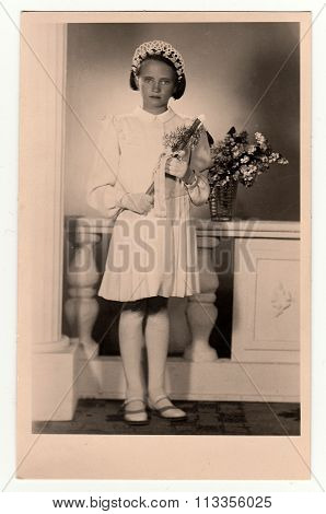 Vintage photo of a young girl -  her first holy communion. The thirties.