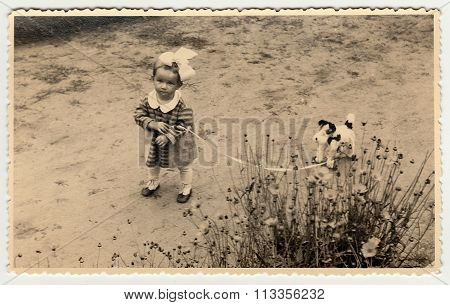A small girl with toy dog. Vintage photo was taken in early forties