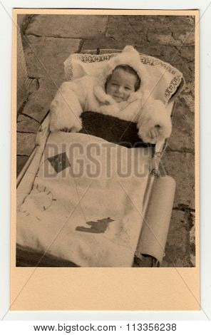 A baby girl in a pram (baby carriage) . Vintage photo was taken in early forties.