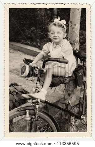 A small girl on bike. Vintage photo was taken in Hodonín (The Czechoslovak  Republic). Early forties