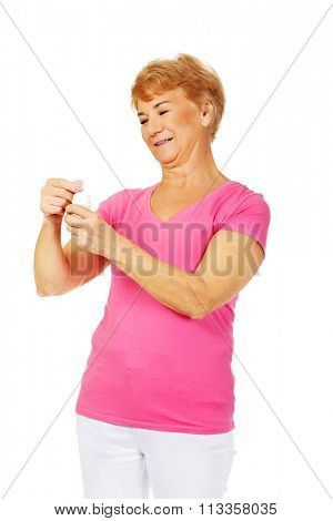 Smiling senior woman holding jar of pills.