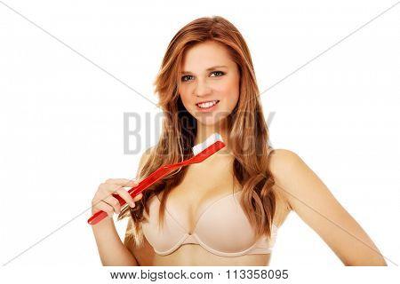 Woman brushing her teeth with huge toothbrush.