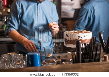 Two people standing behind the bar and prepare desserts