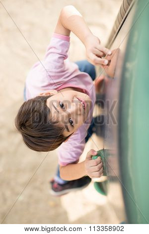 Little boy climbing on the rope at playground