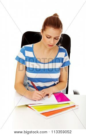 Teenage woman doing homework behind the desk.