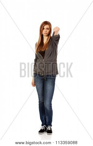 Young unhappy teenage woman showing thumb down.