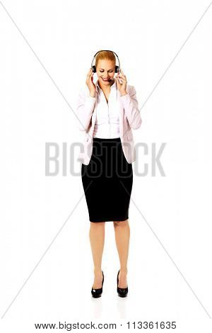 Young woman helpline operator is trying to hear something through headphones.