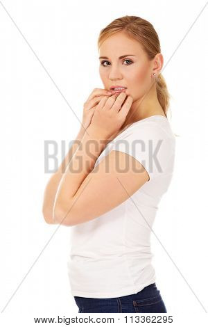 Stressed young woman biting nails.