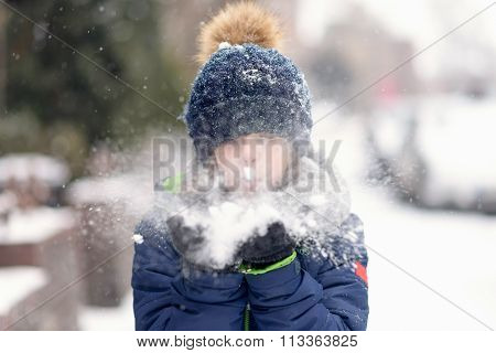 Young Girl Blowing Fresh Snow