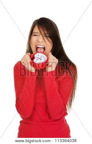 Angry student woman with alarm clock.
