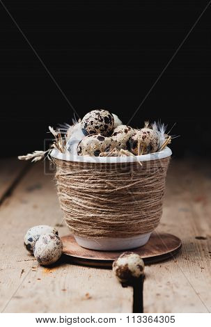 Quail eggs in in a pot with dry straw on a wooden table