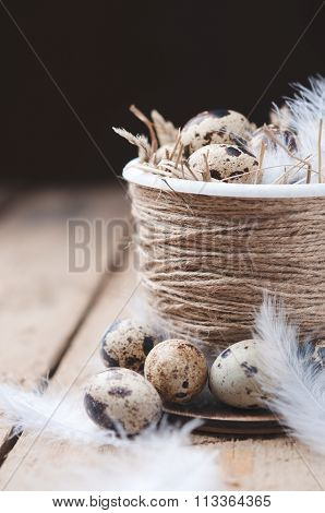 Quail eggs in Easter pot on a wooden table.A darker background.