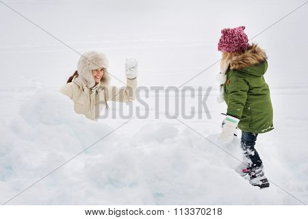 Portrait Of Happy Mother And Child Playing Snowball Fight