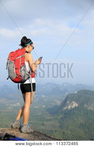 young woman hiker use cellphone on mountain peak