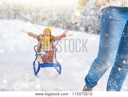 Child sledding. Parent rolls the child on a sled. Little girl enjoying a sleigh ride. Family plays outdoors in snow. Outdoor fun for family winter vacation.