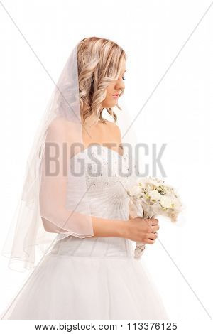 Vertical shot of a worried young bride walking with a wedding flower and looking down isolated on white background