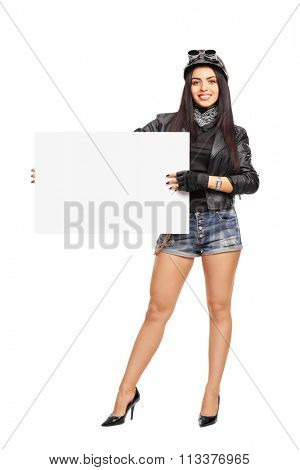 Full length portrait of a young female biker holding a blank white signboard and looking at the camera isolated on white background