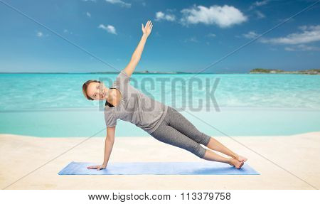 woman making yoga in side plank pose on beach