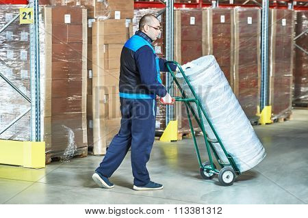 Warehouse worker man with delivery cart moving big heat insulation roll in storehouse
